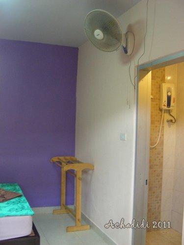 Напротив кровати сушилка, вентилятор и ванная с раздвижными дверями, на фото видно бойлер