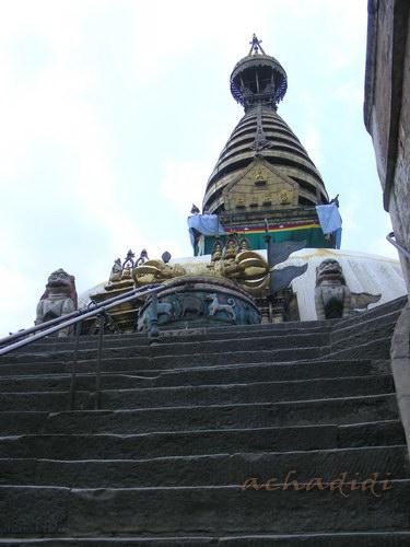 На верху лестницы видны ступа и ваджра